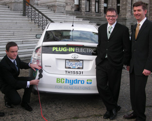 Minister Penner (left) demonstrates how easy it is to recharge a new plug-in hybrid electric vehicle