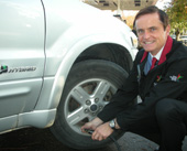 Minister Penner adds air to the tires of his hybrid vehicle